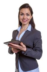 Lachende Geschäftsfrau im grauen Blazer mit Tablet