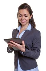 Geschäftsfrau im grauen Blazer surft mit Tablet