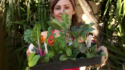 Happy woman holding vegetables, getting ready to garden