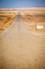 Country road, blank billboard and desert landscape