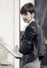 Young fashion business woman in leather jacket with clipboard