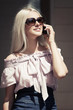 Happy young blond fashion woman calling on mobile phone