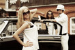 Young fashion blond woman at the retro car