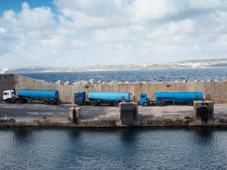 Tankers lined up on a cement wharf