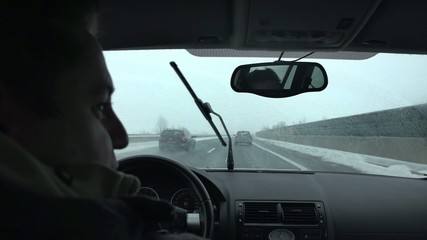 Driver tunrs over and speaks about something while driving on the highway