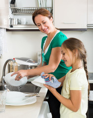 Daughter with mother washing dishes