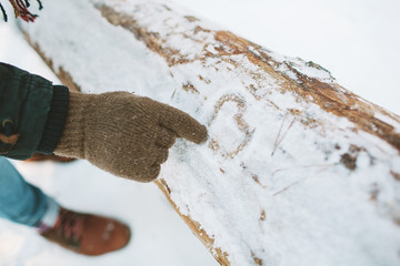 Man draw heart symbol on snow in forest