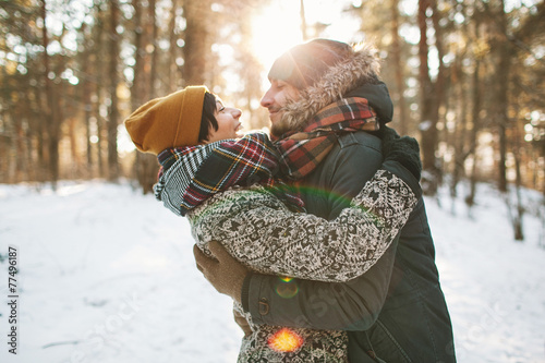 Leinwandbild Motiv Young hipster couple hugging each other in winter forest