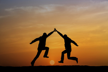 Two man holding for hands and jumping.