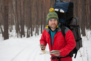man with phone and map in hands traveling winter forest