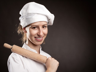 young woman chef holding a rolling pin