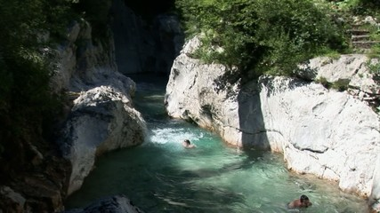 Boys jump into a cold Alpine stream and swim for a while