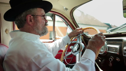 Old farmer is driving a vintage car