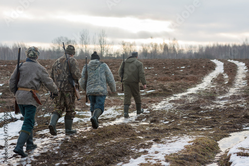 Fotobehang Jacht Group of hunters walking on the field in winter