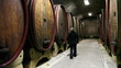Shot of a women checking the barrels in the wine cellar