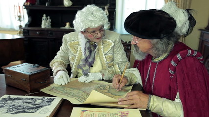Close shot of two medieval men talking about old map