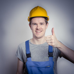 Glücklicher Bauarbeiter zeigt Daumen