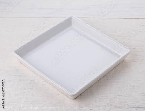 Empty white ceramic plate on wooden table - 77501325