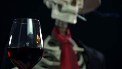 Focus shift from a glass of wine to the skeleton