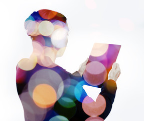 Woman with digital tablet composited with images of lights