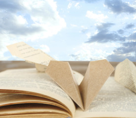 Origami airplanes on book on sky bakground