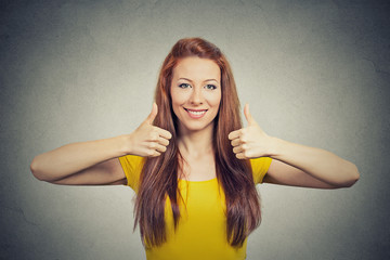 Happy smiling woman with thumbs up gesture grey background