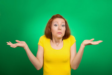 puzzled clueless woman shrugs shoulders green background