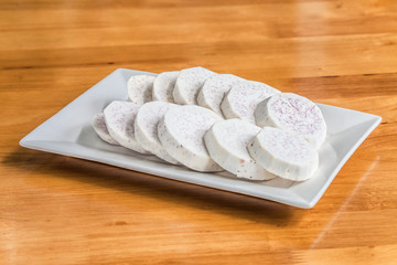 Taro slice on rectangle dish over the wooden table