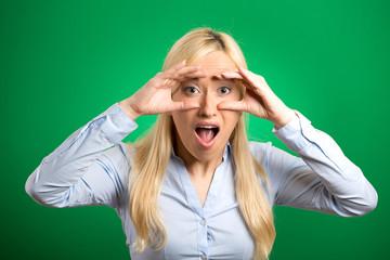 surprised woman peeking looking through binoculars