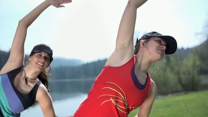 Close Up of Two Fit Girls Stretching For Running