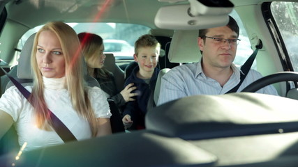 a young, beautiful and frightened family with two children who are having fun back in the car, while driving in a car to a certain destination