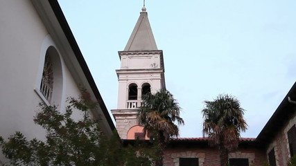 Shot of the church tower and the yard with some palm trees in front