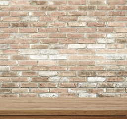 Empty wooden table over brick wall.