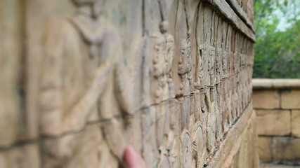 Close up on woman hand touching wall art in ancient city