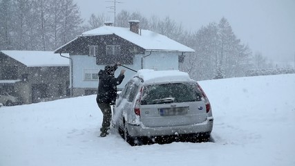 Cleaning the snow off the car's roof
