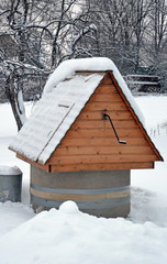 Колодец во дворе деревенского дома под снегом зимним днем