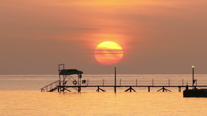 beautiful sunrise over pier in sea - filmed at telephoto lens