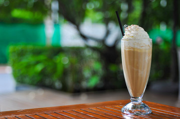 A glass of ice coffee in garden background