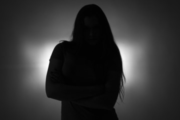 Silhouette of standing teenage girl with long hair