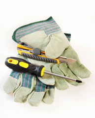 Screwdriver with a cutter lie on protective gloves over white