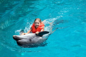 Happy Little Girl Riding the Dolphin in Swimming Pool