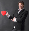 Young handsome man holding red heart