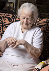 Old woman applying hand cream at home
