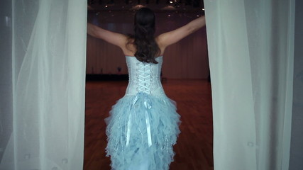 Beautiful woman opening curtains and entering hall