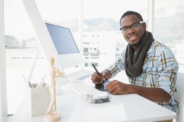 Happy businessman using digitizer at desk