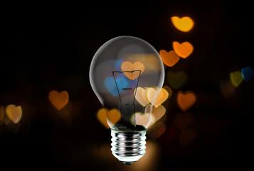 Light bulb with heart shape bokeh background