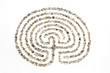 The maze on a white background lined with small sea stones. - 77521957