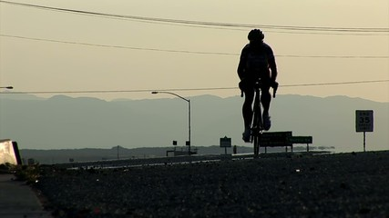 Two competing cyclists approach the camera at the dawn