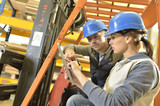 Operator with overseer working in warehouse