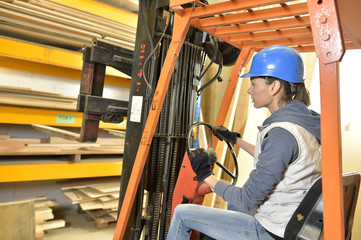 Factory operator in warehouse using storage vehicle